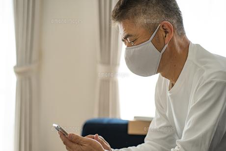 マスクをつけてスマートフォンを見る日本人シニア男性の写真素材 [FYI04774727]