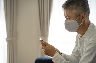 マスクをつけてスマートフォンを見る日本人シニア男性の写真素材 [FYI04774729]