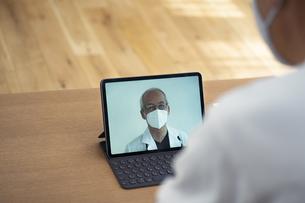 医師とテレビ電話が繋がっているタブレットPCの写真素材 [FYI04774734]