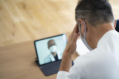 医師とテレビ電話で話すシニア男性患者の写真素材 [FYI04774738]