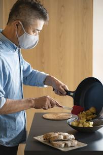 マスクをつけて料理をする日本人シニア男性の写真素材 [FYI04774783]