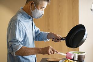 マスクをつけて料理をする日本人シニア男性の写真素材 [FYI04774784]