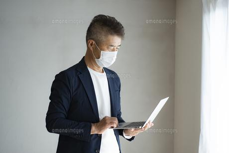 マスクをつけてノートパソコンを見る日本人シニア男性の写真素材 [FYI04774787]