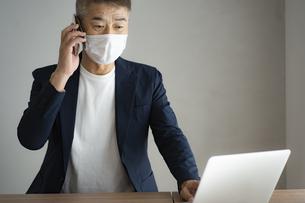 マスクをつけて仕事をする日本人シニア男性の写真素材 [FYI04774790]