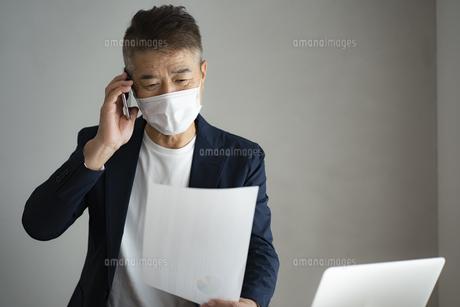 マスクをつけて仕事をする日本人シニア男性の写真素材 [FYI04774791]