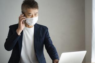 マスクをつけて仕事をする日本人シニア男性の写真素材 [FYI04774792]