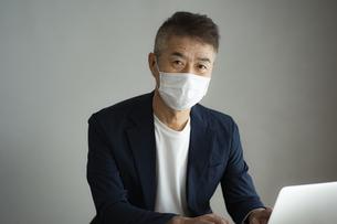 マスクをつけて仕事をする日本人シニア男性の写真素材 [FYI04774793]