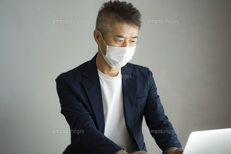 マスクをつけて仕事をする日本人シニア男性の写真素材 [FYI04774794]