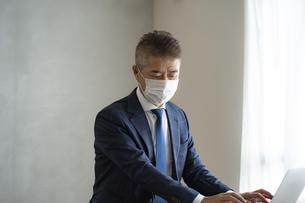 マスクをつけて仕事をするシニア世代の日本人ビジネスマンの写真素材 [FYI04774795]