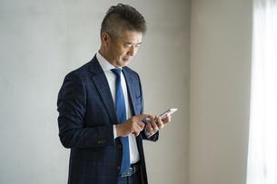 スマートフォンを見るシニア世代の日本人ビジネスマンの写真素材 [FYI04774796]