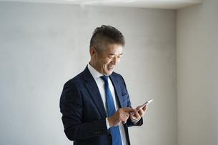 スマートフォンを見るシニア世代の日本人ビジネスマンの写真素材 [FYI04774797]