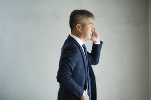 スマートフォンで話すシニア世代の日本人ビジネスマンの写真素材 [FYI04774798]