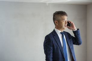 スマートフォンで話すシニア世代の日本人ビジネスマンの写真素材 [FYI04774799]