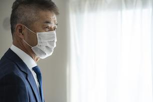 マスクをつけたシニア世代の日本人ビジネスマンの写真素材 [FYI04774800]