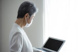 マスクをつけてノートパソコンを見るシニア世代の日本人キャリアウーマンの写真素材 [FYI04774802]