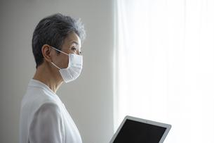 マスクをつけたシニア世代の日本人キャリアウーマンの写真素材 [FYI04774803]