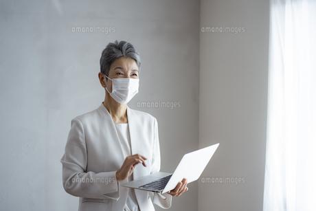 マスクをつけてノートパソコンを持つシニア世代の日本人キャリアウーマンの写真素材 [FYI04774804]