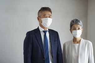 マスクをつけたシニア世代のビジネスマンとビジネスウーマンの写真素材 [FYI04774807]