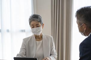 マスクをつけてミーティングをするシニア世代のビジネスウーマンの写真素材 [FYI04774811]