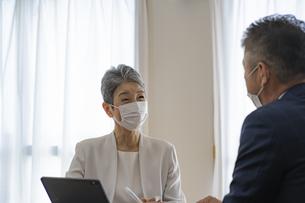 マスクをつけてミーティングをするシニア世代のビジネスウーマンの写真素材 [FYI04774812]