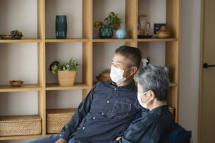 マスクをつけてソファでくつろぐ日本人シニア夫婦の写真素材 [FYI04774819]