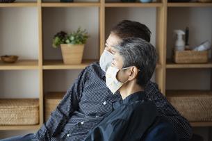 マスクをつけてソファでくつろぐ日本人シニア夫婦の写真素材 [FYI04774825]