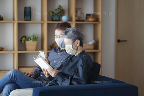 マスクをつけてソファでくつろぐ日本人シニア夫婦の写真素材 [FYI04774826]