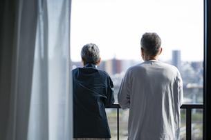 ベランダから外を眺めるシニア夫婦の後ろ姿の写真素材 [FYI04774827]