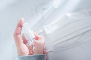携帯用の消毒液スプレーを手で持つ様子。の写真素材 [FYI04775539]