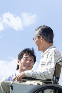 車椅子に座るシニア男性と笑顔の男性の写真素材 [FYI04776319]