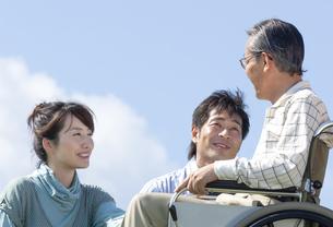 車椅子に座るシニア男性と笑顔の夫婦の写真素材 [FYI04776321]