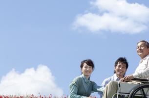 車椅子に座るシニア男性と笑顔の夫婦の写真素材 [FYI04776325]