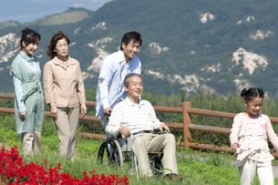 車椅子に座るシニア男性と笑顔の家族の写真素材 [FYI04776335]