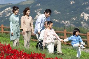 車椅子に座るシニア男性と笑顔の家族の写真素材 [FYI04776336]