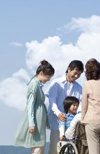 車椅子に座るシニア男性と笑顔の家族の写真素材 [FYI04776338]