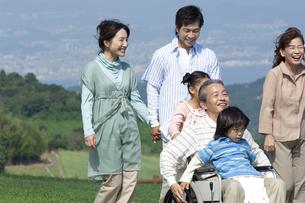 車椅子に座るシニア男性と笑顔の家族の写真素材 [FYI04776341]