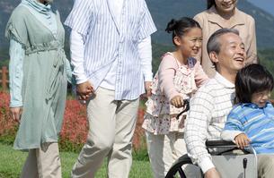 車椅子に座るシニア男性と笑顔の家族の写真素材 [FYI04776348]