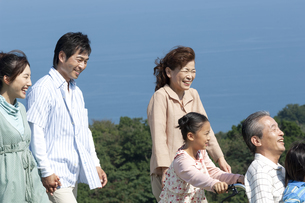 車椅子に座るシニア男性と笑顔の家族の写真素材 [FYI04776351]