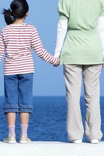 防波堤に立つ女の子と母親の写真素材 [FYI04776494]