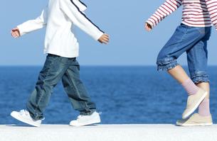 防波堤を歩く男の子と女の子の写真素材 [FYI04776498]
