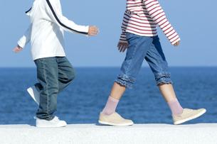 防波堤を歩く男の子と女の子の写真素材 [FYI04776499]