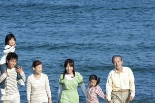 海辺を歩く3世代家族の写真素材 [FYI04776508]