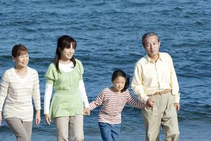 海辺を歩く3世代家族の写真素材 [FYI04776509]