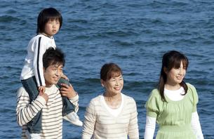海辺を歩く3世代家族の写真素材 [FYI04776510]