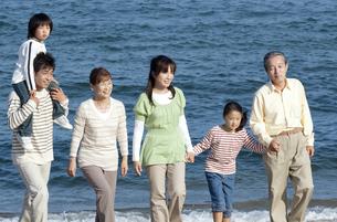 海辺を歩く3世代家族の写真素材 [FYI04776511]