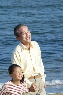 海辺を歩く孫と祖父の写真素材 [FYI04776513]