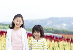 花畑の前の立つ女の子と男の子の写真素材 [FYI04776561]