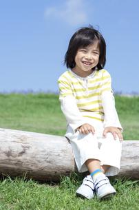 木のベンチに座る男の子の写真素材 [FYI04776569]