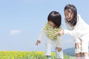 花畑で遊ぶ女の子と男の子の写真素材 [FYI04776578]