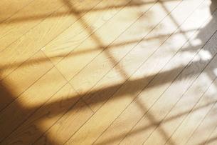リビングの床に映る夕暮れの窓の影の写真素材 [FYI04776605]